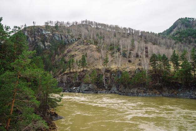 Montanhas em tons de terra com cobertura florestal e rio da montanha em tempo de primavera.