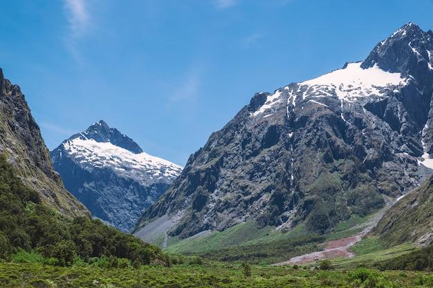 Montanhas enormes com neve no parque nacional de fjordland na nova zelândia