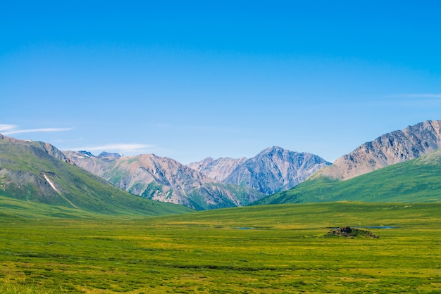 Montanhas gigantes com neve acima do vale verde sob o céu azul claro.