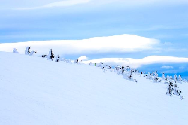 Montanhas na neve em um fundo de nuvens no inverno