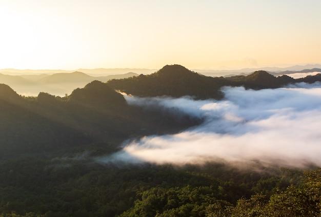 Montanhas na névoa do nascer do sol