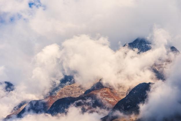 Montanhas nas nuvens na noite nublada no nepal. paisagem com belas pedras altas e céu nublado dramático ao pôr do sol