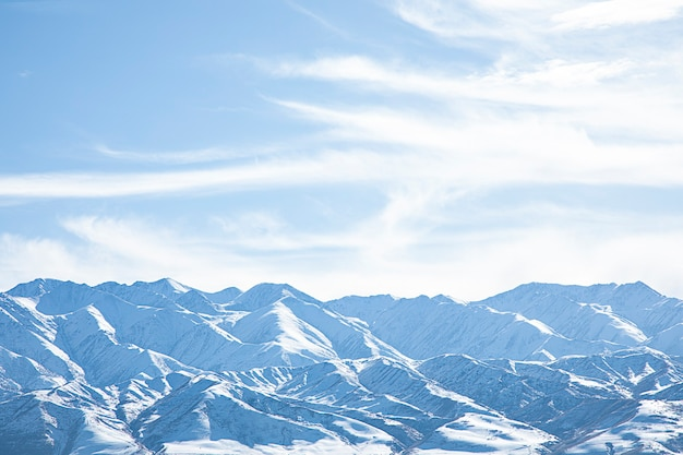 Montanhas nevadas com céu azul e nuvens