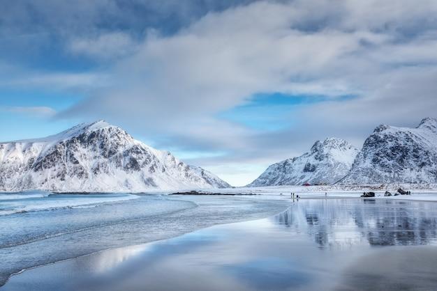 Montanhas nevadas e céu azul com nuvens refletidas na água no inverno