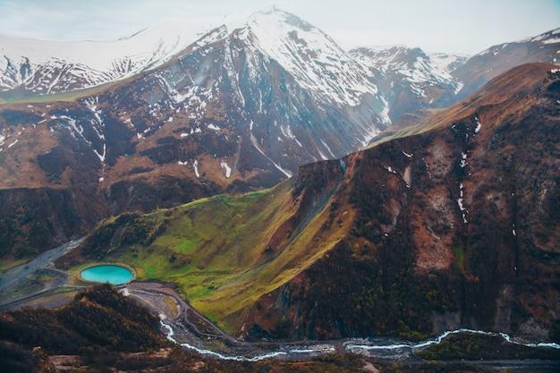 Montanhas nevadas e lago azul no vale verde
