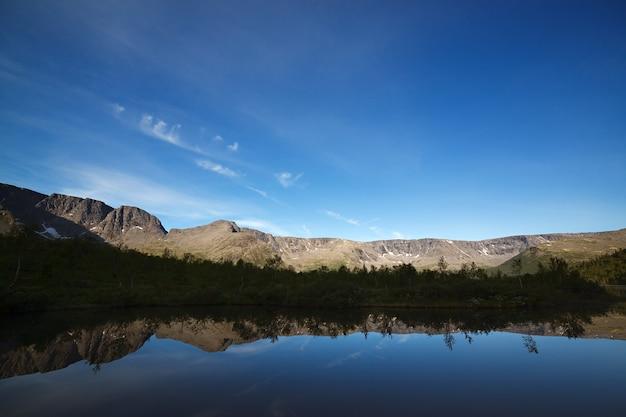 Montanhas refletidas na superfície lisa do lago ao amanhecer