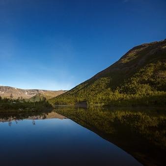 Montanhas refletidas na superfície lisa do lago ao amanhecer.