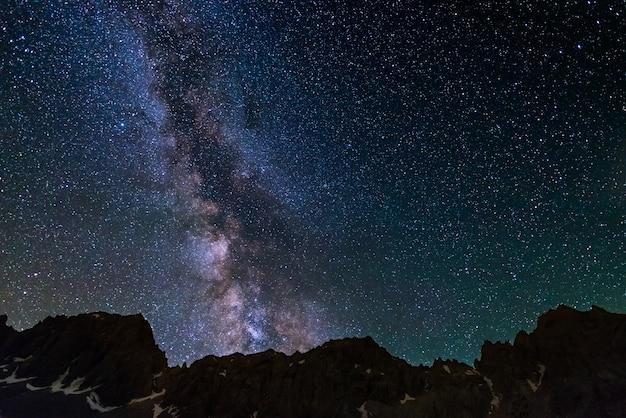 Montanhas rochosas do céu estrelado da via látea na alta altitude nos cumes.