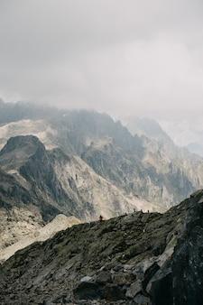 Montanhas rochosas e uma pessoa de pé sobre elas