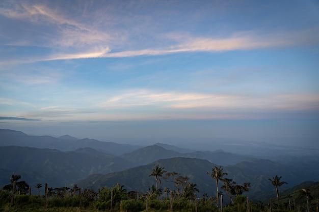 Montanhas tropicais e primeiro plano de palmeiras durante o nascer do sol. conceito de viagens e aventura.