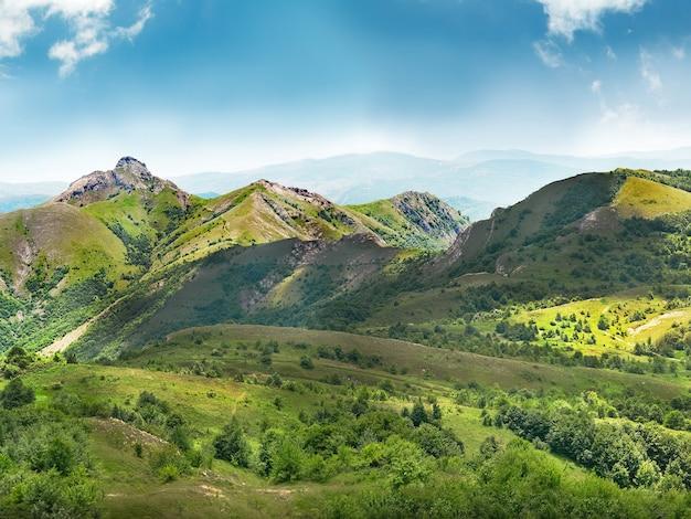 Montanhas verdes cobertas de floresta no céu azul