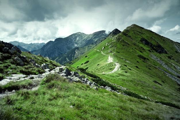 Montanhas verdes e céu nublado escuro.