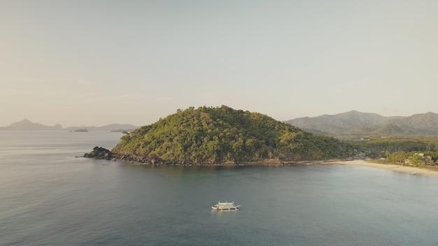 Montanhas verdes na baía do mar com barcos aéreos. resort tropical na praia de areia. palmeiras verdes em