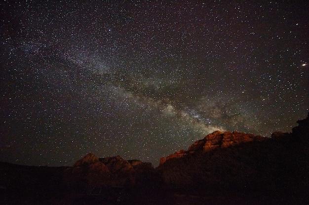 Montanhas vermelhas do deserto com estrelas da via láctea