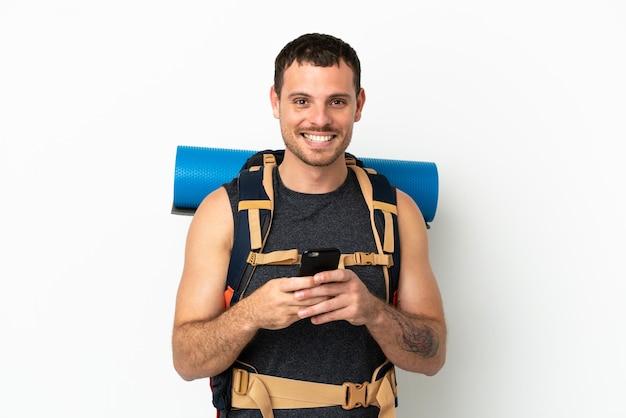 Montanhista brasileiro com uma grande mochila sobre fundo branco isolado enviando mensagem pelo celular