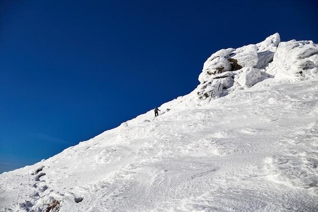 Montanhista de homem caminhando na colina coberta de neve fresca. montanhas carpathian