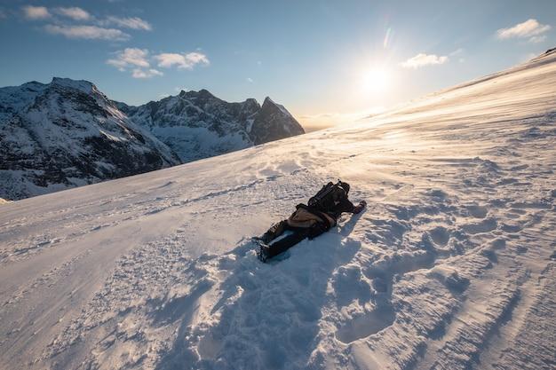 Montanhista de homem escalando e rastejando no pico da montanha de neve com sol à noite em ryten mount. conceito de esperança e desespero