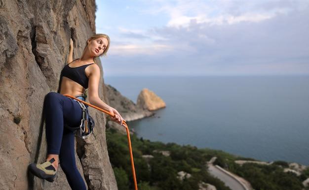 Montanhista de rocha da mulher no penhasco de rocha pendendo sobre íngreme.