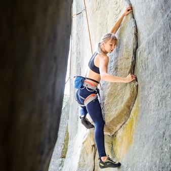 Montanhista fêmea louro desportivo que escala a parede de pedra íngreme na natureza, com a corda envolvida.