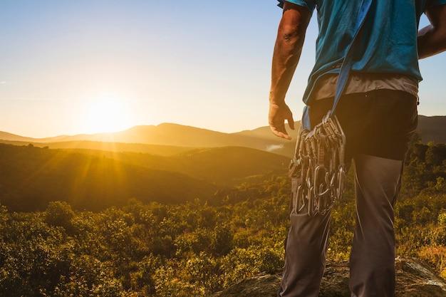 Montanhista olhando para uma paisagem do por do sol