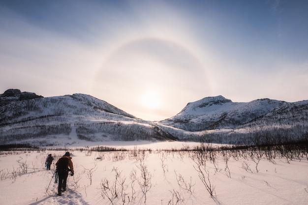 Montanhistas caminhando em vale de neve com auréola natural de sol no inverno
