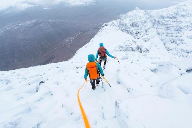 Montanhistas escalando um liathach ridge nevado na escócia