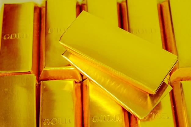Montão das barras de ouro isoladas em um conceito branco da operação bancária do fundo.
