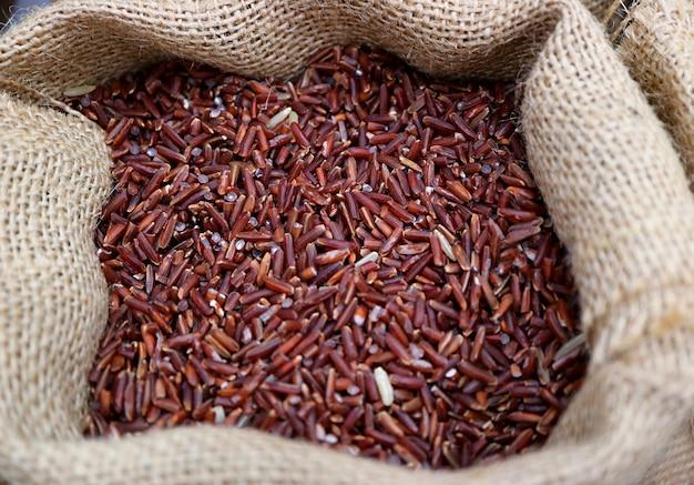 Montão de arroz de arroz de cor roxo profundo cru em um saco de cânhamo natural