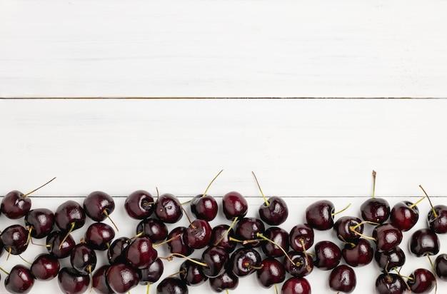 Montão de cerejas vermelhas e pretas maduras frescas no assoalho de madeira branco da prancha para o fundo.