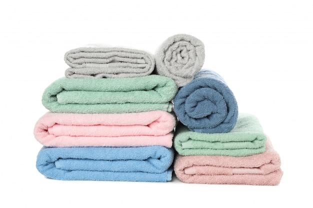 Montão de toalhas dobradas da cor isoladas no branco