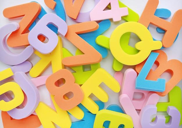 Montão desarrumado do fundo de letras e de números do alfabeto da borracha de esponja.