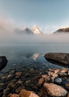 Monte assiniboine com pedras na neblina no lago magog pela manhã no parque provincial