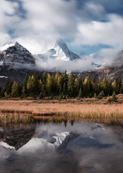 Monte assiniboine com reflexão da floresta do outono no lago magog no parque provincial