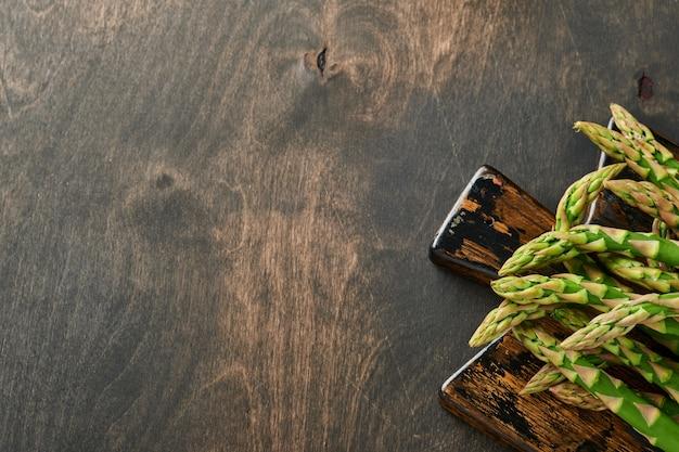 Monte de aspargos verdes frescos prontos para cozinhar em fundo preto de madeira velho