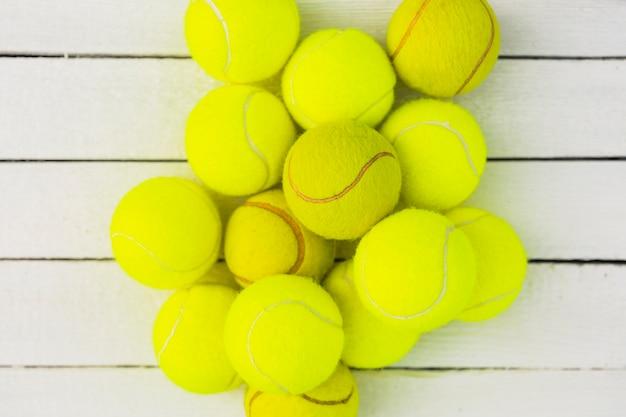 Monte de bolas de tênis verde na mesa de madeira