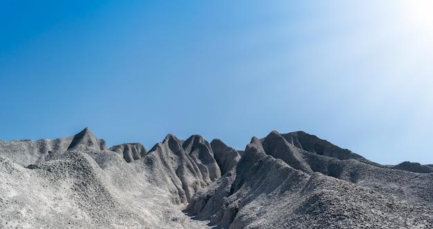 Monte de cascalho, esmagado por sulcos de erosão hídrica.