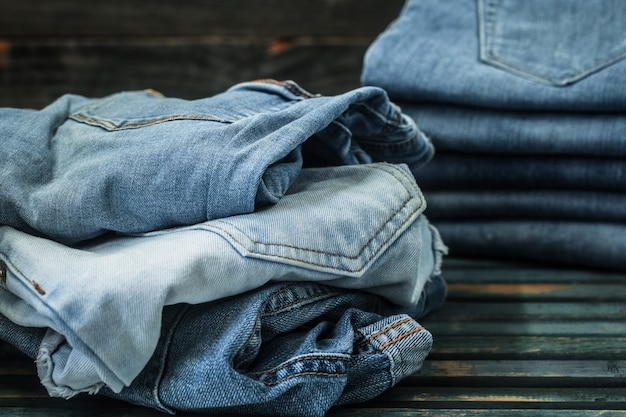 Monte de jeans em fundo de madeira, roupas da moda