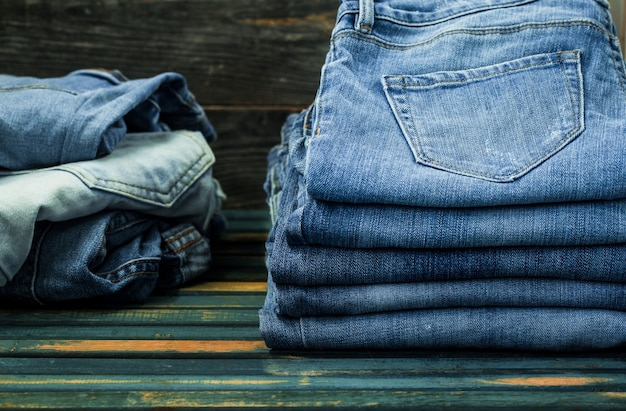 Monte de jeans na parede de madeira, roupas da moda