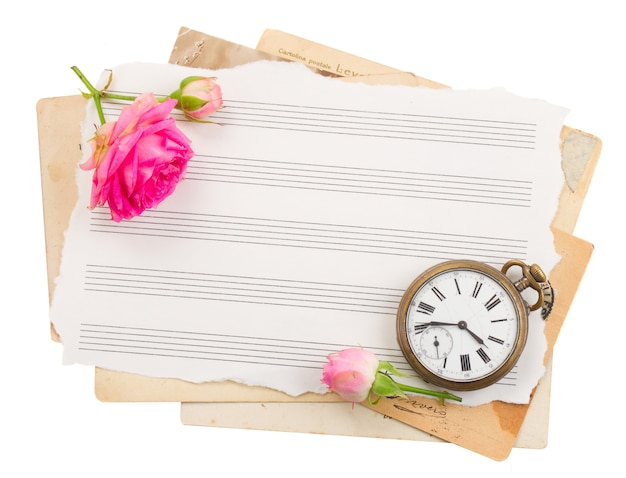 Monte de papéis antigos com relógio antigo e rosa
