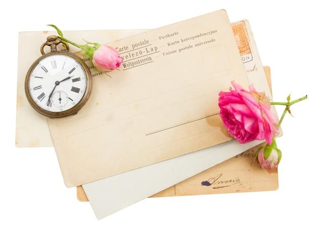 Monte de papéis velhos com rosas e um relógio antigo
