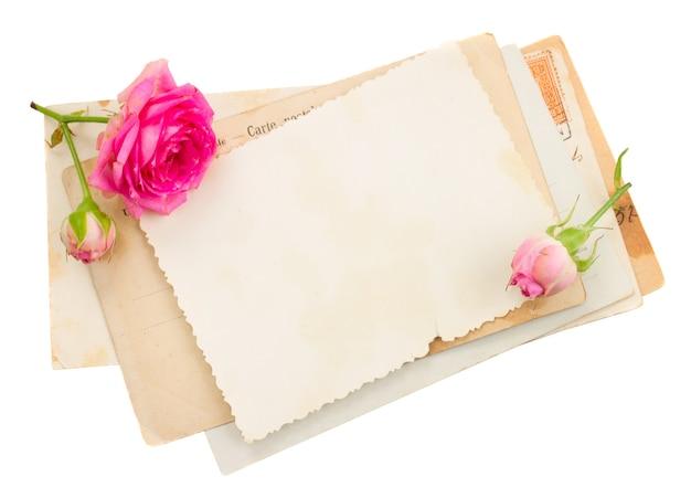 Monte de papéis velhos com rosas isoladas em branco