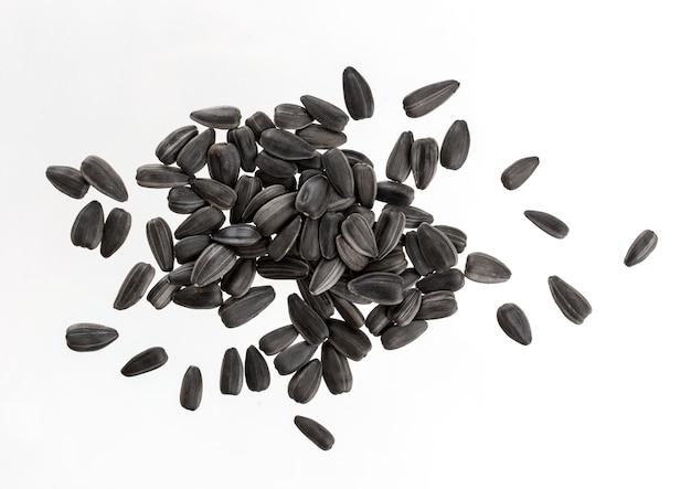 Monte de sementes de girassol pretas isoladas no branco