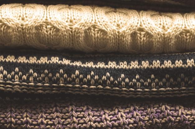 Monte ou pilha de suéteres de lã tricotados foto sombria com texturas
