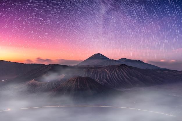 Monte vulcão ativo, batok, bromo, semeru com estrelada e nevoeiro ao amanhecer