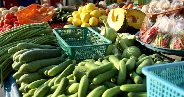Montes de legumes frescos maduros e frutas exóticas colocados na tenda em dia ensolarado no mercado de rua