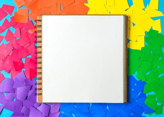 Montes de papel em cores brilhantes lgbt e notebook