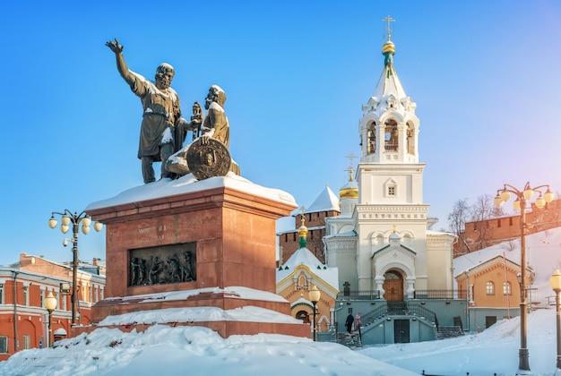 Monumento a minin e pozharsky e a torre do sino da igreja perto das muralhas do kremlin de nizhny novgorod