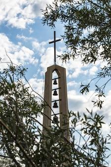 Monumento religioso com cruz e sinos