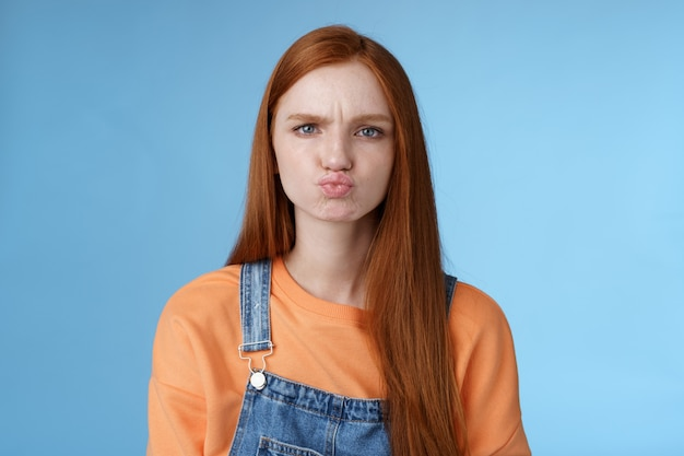Moody desagradou namorada pegajosa ruiva olhos azuis fazendo beicinho chateado chateado ofendido franzindo a testa fazendo careta mostrando atitude em pé desapontado insatisfeito fundo azul, reclamando
