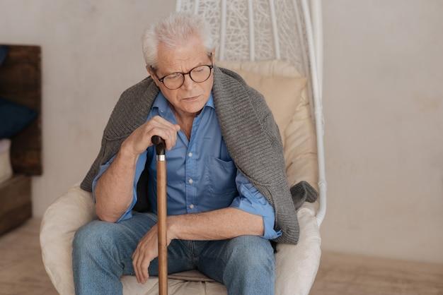 Moody triste homem infeliz apoiado em sua bengala e pensando sobre seu passado enquanto descansava na poltrona